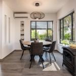 שולחן דק וכסאות במראה מינימלי . תאורה מותאמת שיוצרת צל יפהפה על התקרה.